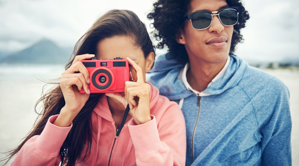 Fashionable hipster couple taking retro camera photo at beach